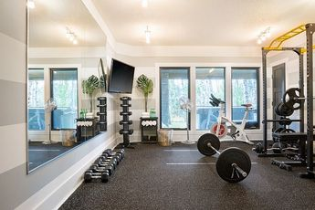 Home Gym The mounted TV is great for watching spin classes or YouTube workout videos – it's like having a built-in trainer #homegym #modernbasementgym