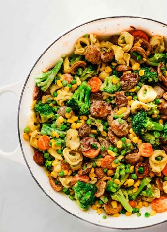 Need easy chicken recipes for dinner to feed your family? This easy chicken sausage pasta skillet meal is perfect! Just add veggies, tortellini and mix in a creamy garlic sauce for a crowd-pleasing dinner that can be prepared in under 30 minutes. | via happymoneysaver.com | #chicken #sausage #pasta #dinner #makeahead #creamy #onepan #skillet #veggies #sauce #lunch