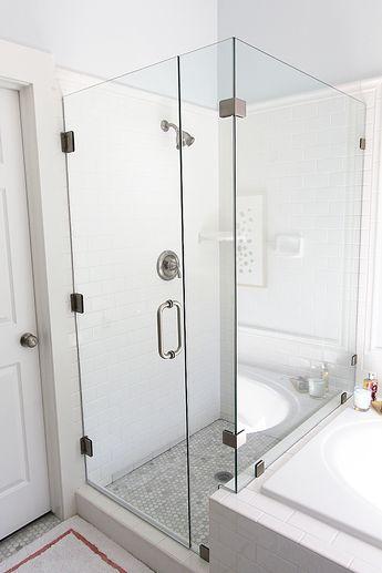 frameless glass shower next to tiled tub. like the border around the edge of the subway tile