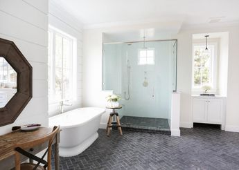Gray+tile+floors+provide+contrast+in+this+ultra-bright+bathroom.+The+gray+tiles+form+a+herringbone+pattern,+creating+movement+in+the+clean,+crisp+space.+A+glass-enclosed+shower+makes+the+spacious+room+feel+even+larger.
