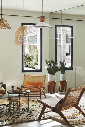 Inspirez-vous de ces idées déco et aménagement ! Faites entrer la lumière naturelle dans votre salon en y installant de grandes fenêtres modernes et design. Une cloison miroir est l'astuce parfaite pour agrandir l'espace ! Et pour parfaire le tout, misez sur du carrelage effet béton blanc pour rendre l'atmosphère encore plus lumineuse.