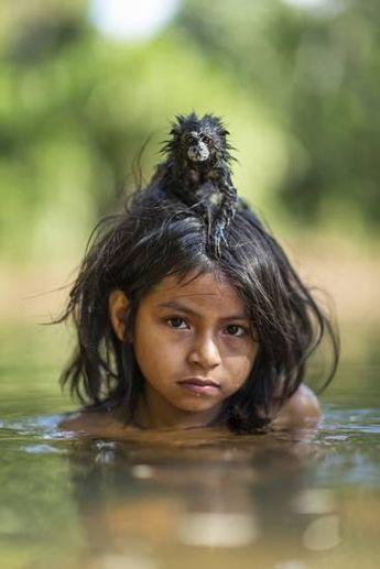 A Pet Saddleback Tamarin Hangs on Tight to a Matsigenka Girl as She Swims in the Yomibato River Photographic Print by Charlie Hamilton James