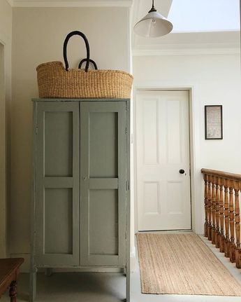 Antique white pendant light. White walls. Grayish flood. White doors. Basket. Dusty blue storage cabinet. Wood bench.