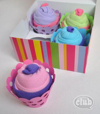 En roulant un vêtement pour bébé, elle réalise un emballage cadeau cupcake parfait!