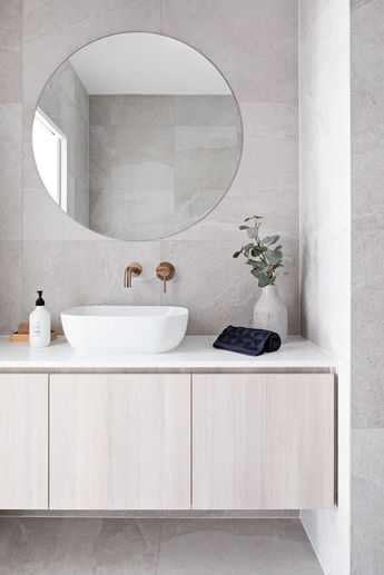 Clean lines and large format grey tile covers the floor and walls. A round frameless mirror hangs over a white sink with brass wall mounted bathroom sink faucet. The flat paneled vanity is wall mounted and has a thin white countertop