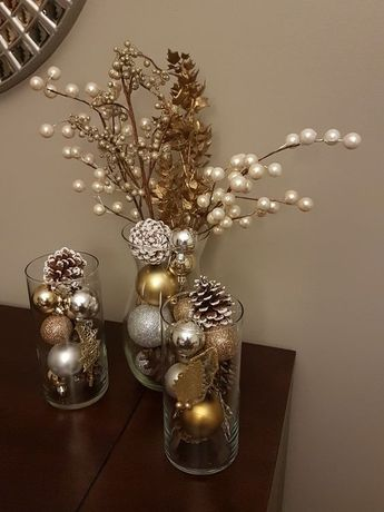Golden, silver and copper ornaments with pinecones in the vase.