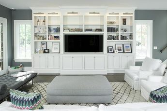 White and charcoal gray living room features a a pair of white slipcovered chairs facing a gray ottoman atop a beni ourain rug facing a white built-in tv cabinet illuminated by nickel picture lights.