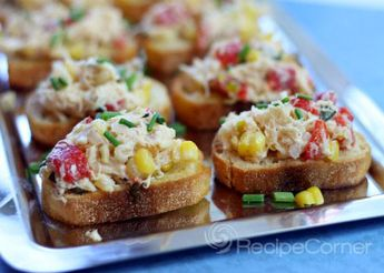 These fancy hor d'oeuvres are super easy and delicious. Grilled corn, roasted red peppers, shallots, and crab are sauteed in a white wine and goat cheese sauce. This rich and creamy mixture sits elegantly on top of French baguette slices and is garnished with chives.