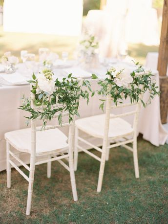 Whimsical greenery for the white chairs.