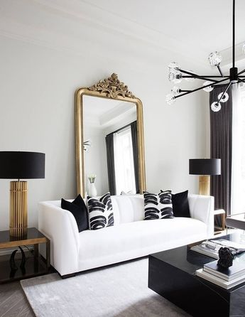 Absolute GLAM! Gold black and white glam condo apartment, featuring a white leather sofa and a vintage gold floor mirror in the back. Loving the solid square black marble coffee table! Shop the look in this post! #modernglam #condostyle #apartmentstyle # #ShopStyle #shopthelook #blackandwhite #interiordesign #interiordecor #homedesign #decor #homeremodel