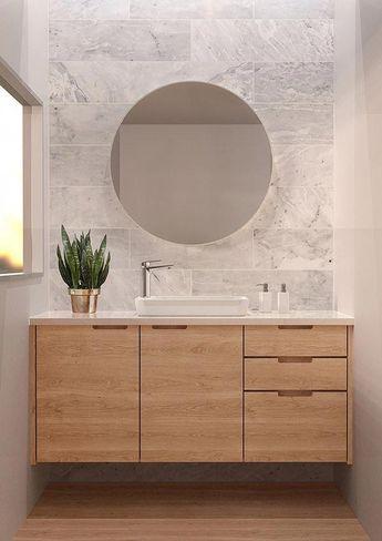 Scandinavische badkamer inspiratie met grijze natuursteen achtige tegels. Daarnaast een heel mooi houten meubel met diverse lades. De ronde spiegel maakt het helemaal af. Ook zo'n prachtige badkamer? Klik dan op de foto! #Bathroomgrey