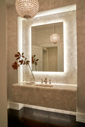 The Renwick Small Sphere Chandelier by AERIN injects instant elegance into this minimalist powder room. Photography by Nathan Schroder.
