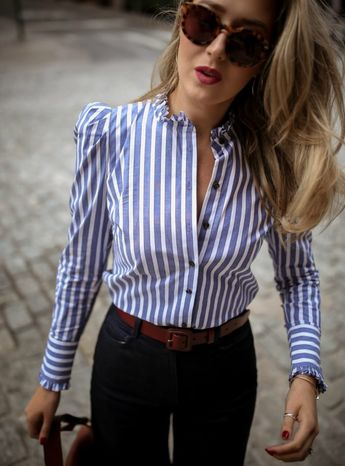 Up close image of NYC style blogger wearing a blue striped button down shirt with puff sleeves, wide leg pants, brown belt and sunglasses.