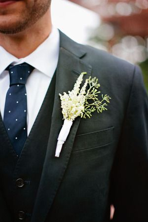 A classic charcoal gray groom's suit featuring a navy polka dot tie and white boutonniere.   Simple Elegance Floral & Event Design, Wisconsin
