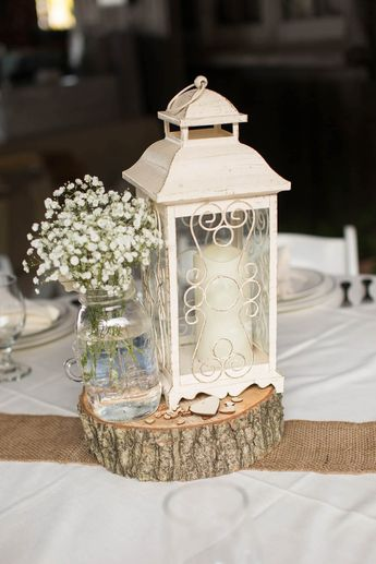Rustic wedding centerpiece with wood block, white lantern, burlap, mason jar and baby's breath.