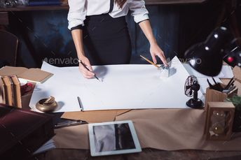 Architect working on drawing table in office by master1305. Architect woman working on drawing table in office or home. Studio shot
