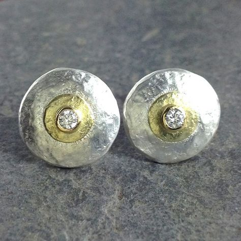 Silver and gold mixed metal diamond stud earrings. These little earrings have been cut from thick sterling sheet and hammered for shape and texture , they feature a small disk and setting in yellow gold and are set with sparkly little round b.