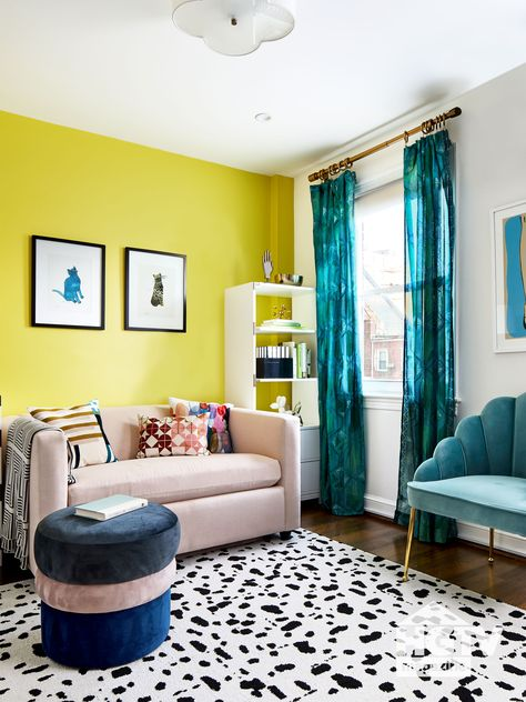 Turquoise accessories and yellow walls pair perfectly with a blush couch and a black and white rug in this colorful living room. See more on HGTV.com.