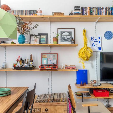 Apartamento pequeno com espaço otimizado para aproveitar a luz natural tem muitas plantas e prateleiras. Entre as peças queridinhas dos moradores estão o arquivo de metal, usado como sapateira, as luminárias coloridas e até uma rede de balanço