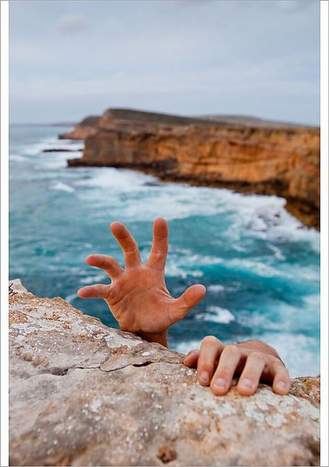 A1 Poster. Hands reaching up to grip a cliff. Dangerous ocean in