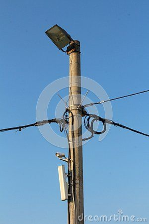 Concrete Utility Pole With Multiple Black Electrical Wires Small White Camera Cell Phone Tower Transmitter Metal Spikes White Camera Reflectors Metal Spikes