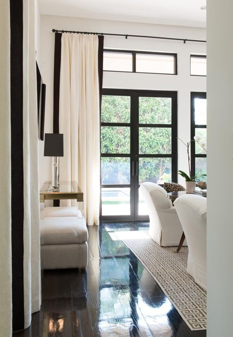 Black windows, dark wood floor combine beautifully with creamy fabrics in furniture and draperies.