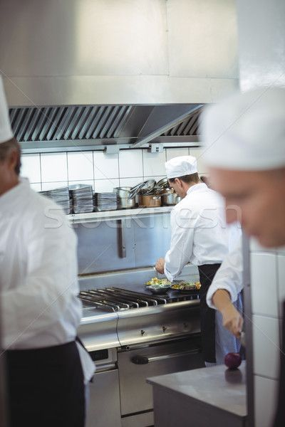 Chefs Preparing Food In The Commercial Kitchen Stock Photo C