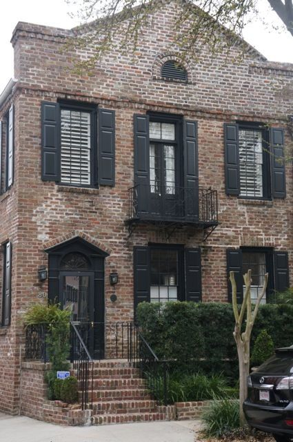 Brown brick, black window trim and shutters
