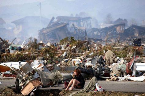 Une femme est assise au milieu des débris causés par un violent séisme et par le tsunami qui a suivi, à Natori, au nord du Japon en mars 2011