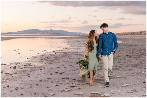 Couple walking on the beach at sunset during Antelope Island Engagement with bouquet | Antelope Island Engagements | Utah Wedding Photographers | Jessie and Dallin Photography  #utahwedding #utahengagement #engagementphotography #engagmentsession #engagementphotos #uniqueengagement #weddingflorals #beachengagment #engagmentsunset #couplesphotography #brideandgroom #romanticengagement #elegantengagement #utahweddingphotographer