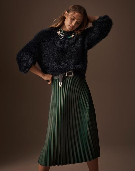 What a chic combo. A woman wearing a black top paired with a long dark green pleated skirt. Image by Marks & Spencer.