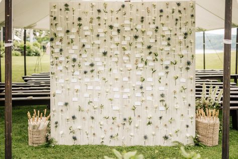 We love this spring garden-inspired place card wall covered in local flowers from the farmer's market, each attached to a card that directs guests to their tables! Click through for more rustic wedding ideas. #rusticwedding #flowerwall #weddingflowerwall #weddingplacecards #escortcards #gardenwedding