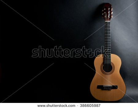 Acoustic Guitar On A Black Background With Copy Space