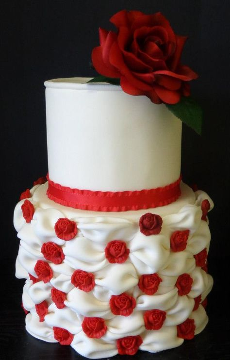 A beautiful dual tier, fondant covered cake topped with a large red rose and with smaller red roses accenting a flowing, billow skirt design. Created by Sweet Pea Cake Co. of Colorado Springs.