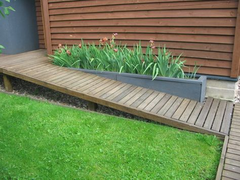 Possible something like this at the bottom of the ramp to the back garden? Using raised planter to channel people away from the pond.
