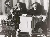 """Read FDR's Famous 'Day of Infamy' Speech: President Roosevelt delivers the """"Day of Infamy"""" speech to a joint session of Congress on December 8, 1941. Behind him are Vice President Henry Wallace (left) and Speaker of the House Sam Rayburn. To the right, in uniform, is Roosevelt's son James."""