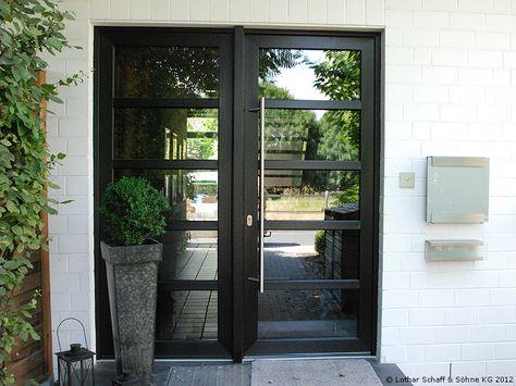 zweiteilige Hauseingangstür mit schwarzen Riegeln aus Kunststoff, dunklem verspiegeltem Glas im schlichten Design
