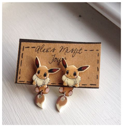 Everyone loves Eevee! These cute earrings make it look as though Eevee is hanging on to your ear! They come in two pieces, with eevees head on