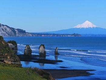 Mt. Taranaki in the background, Three sisters beach in the foreground with Elephant Rock to the far left.
