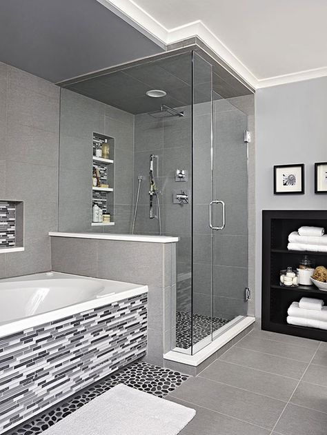 Sheathed in oversize ceramic tile, the shower is grounded with a textured river rock floor. A rain-style showerhead and handheld wand enhance showering. The same linear tile on the vanity backsplash covers the tub surround and niche, adding a third layer of tile style.
