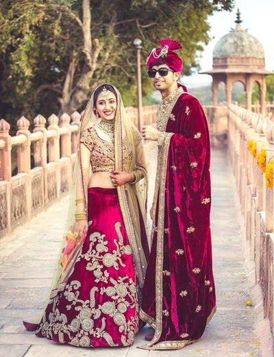 Candid Couple Shots - Bride in a Marsala Lehenga | WedMeGood | Marsala Velvet Wedding Lehenga with Gold Embroidery, Marsala Blouse and Beige Net Dupatta, Groom in a Gold Sherwani with a Velvet Marsala Shawl  #wedmegood #indianbride #indianwedding #marsala #velvet #indiangroom #coupleshot