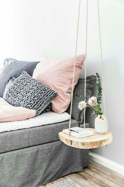 a cute hanging nightstand of rope and a wood slice for a natural touch