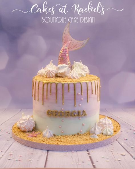 Gorgeous pastel pink, aqua and lilac watercolour mermaid themed cake, with gold drips, homemade meringues and handmade fondant and wafer paper mermaid tail coloured with petal dusts, petal dusts and finished with touches of gold.