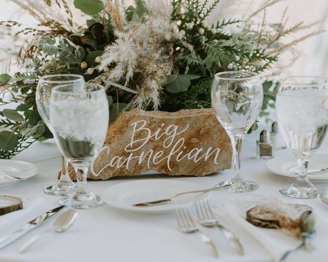 Share your favorite spots with your guest while bringing some nature into your wedding with these hand painted, calligraphy lettered, stone tabletop signs. Perfect for any adventurous themed wedding! Photo by Catherine Lea Photography