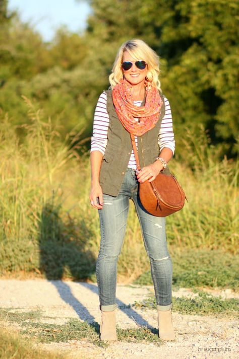For your classic gal-Layer the olive green vest under a long sleeve striped top. To add dimension and texture to the look, add a fun colored scarf. Finish the look with a crossbody bag and neutral booties for a classic look.