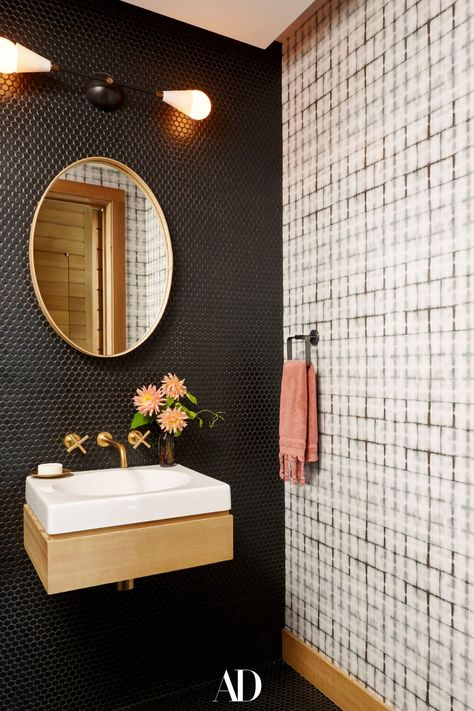 Interior designer Bella Mancini worked with Douglas Wright Architects to craft a contemporary dream home not far from Manhattan. In a powder room, an Apparatus sconce hangs over a Pinch mirror and custom vanity. #bathrooms #bathroomideas #vanity #design #sink #mirror #wallpaper #powderrooms #sconce #Lightfixtures