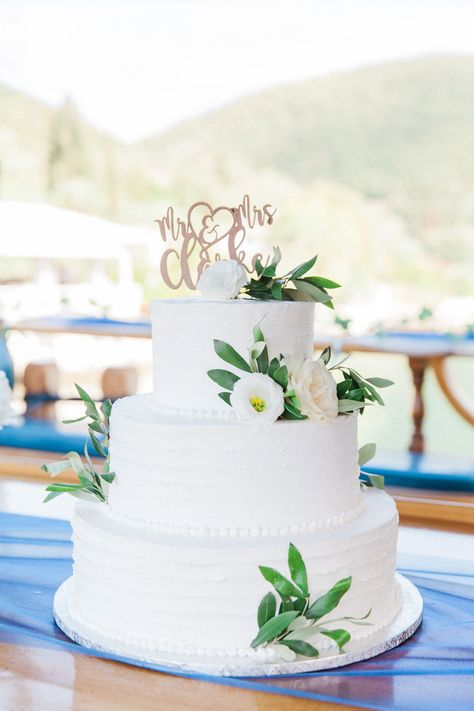 Sail Away with this gorgeous wedding cake decorated with real flowers and a personalised wooden cake topper for the newlyweds on their wedding cocktail cruise in Lefkada onboard the luxury M/S Christina. Planner @lefkasweddings with @maxeenkim photography #destinationweddingcake #greekweddingcake #weddingcakeinspiration