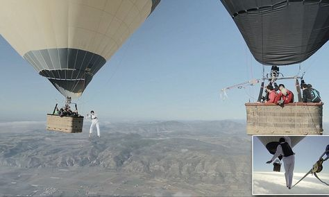 Daredevils tightrope walk between two hot-air balloons in jaw-dropping video