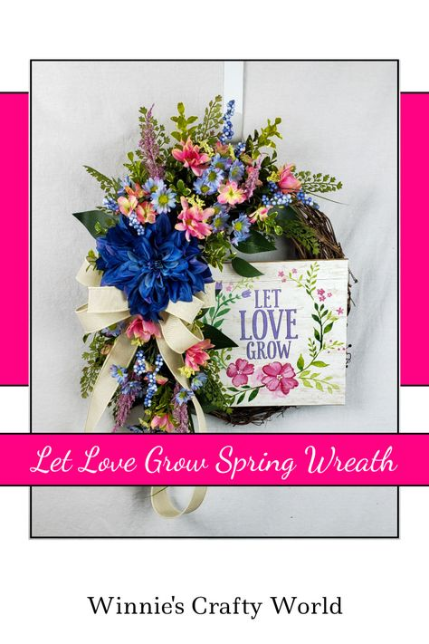 Are you wanting to find a beautiful wreath for your front door? Maybe you are looking for a Mother's Day gift? This might be the perfect wreath for you! #LetLoveGrow #SpringWreath #MothersDayWreath #FrontDoorWreath #FrontPorchWreath #PinkAndBlueWreath #SilkFlowerWreath #GrapevineWreath #WinniesCraftyWorld