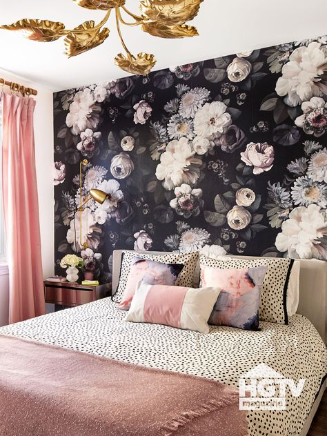 Black and white floral wallpaper sets a chic backdrop for pink and white dotted bedding and golden accessories in this bedroom. See more on HGTV.com.